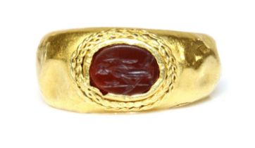A Roman gentlemen's high carat gold cornelian intaglio ring,