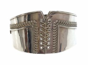 A Victorian sterling silver hinged bangle of corset form,