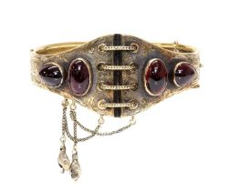 A Victorian gold garnet set hinged bangle, c.1860,
