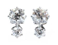 A pair of two stone diamond stud earrings,