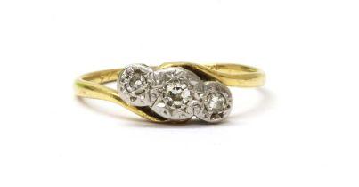 A gold three stone diamond crossover ring,