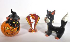 Two Lorna Bailey signed porcelain models of stylised cats, one astride a pumpkin, together with a