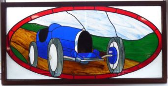 A large multi-coloured stained-glass wallhanging depicting a blue 1920s/30s Bugatti-style racing