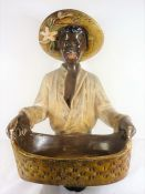 A mid-20th century painted plaster blackamoor-style figure; the smiling figure holds a two-handled