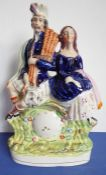 A circa 1870 pottery figure; a Scotsman and his lady seated above a clock, in good condition and