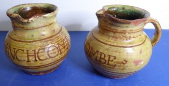 A pair of early Winchcombe Pottery slipware jugs; incised in capitals 'WINCHCOMBE', attributed to