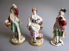 Three Spanish porcelain figures: a barefooted male with a basket of fruits and a female with a