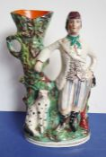 A circa 1870 Staffordshire spill vase; decorated with a figure of a hunter and his seated dog,