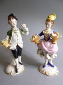 A pair of Continental hand-decorated porcelain figure models: a young boy in green tunic holding a