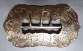 A 19th century American shoe or hat buckle engraved with eagles, flags, cannon and rifles etc.,