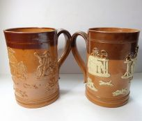 Two similar 19th century salt glaze Doulton Lambeth tankards; typically decorated in relief with