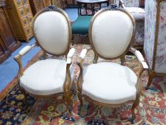 A pair of 19th century spoon back open armchairs in mid / late 18th century French style; the top-