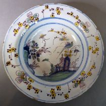 An attractive early 18th century English Delftware soup dish; the border decorated with sprigs and