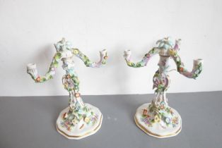 A pair of late 19th century German porcelain three-light candelabra (some damage); the removeable