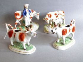 A pair of 19th century Staffordshire cow creamers together with two other similar figures (4)