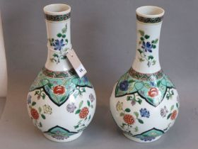 A good pair ofKangxi-style Chinese porcelain bottle vases (19th century); hand-decorated in famille