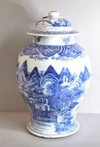 A baluster jar and cover painted in underglaze blue with buildings under towering peaks, the