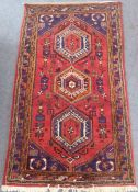 A red ground Hamadan hand knotted rug with three rug with three central lozenges against a red