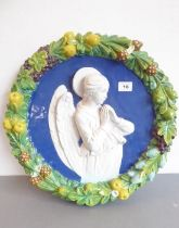 A late 19th/early 20th century polychrome decorated circular pottery wall plaque in the style of
