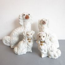 Two pairs of 19th century Staffordshire spaniels with gilded collars (some damage) (the larger pair,