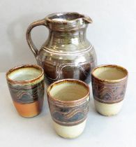 Modern Winchcombe Pottery -a jug(20cm high)and three beakers; each decorated with a wavy-style