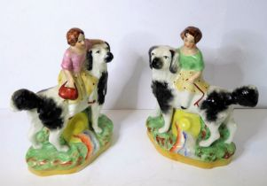 An opposing pair of 19th century Staffordshire figures; two girls riding upon the backs of black and