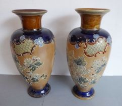 A matched pair of late 19th century Royal Doulton stoneware vases. Flowering necks above baluster-