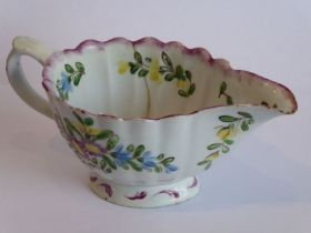 A mid-18th century Bow porcelain cream jug; hand-decorated with floral sprays and enamels above a