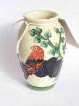 A small modern Moorcroft pottery vase of baluster form, decorated with a parrot upon a plum tree,