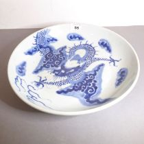 A Chinese porcelain bowl, probably 18th century. Decorated in underglaze blue with a four-clawed