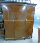 EARLY 20TH CENTURY BOW FRONT INLAID MAHOGANY TRIPLE DOOR WARDROBE WITH FITTED INTERIOR ON SQUARE