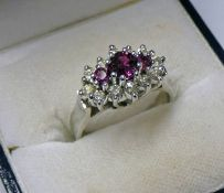 18CT GOLD RUBY & DIAMOND SET RING, THE 3 GRADUATED RUBIES IN A SURROUND OF APPROX 0.