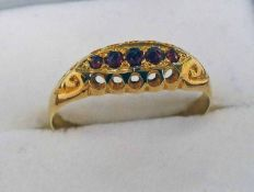 18CT GOLD 5-STONE GARNET SET RING IN A SCROLL MOUNT Condition Report: Ring size: R.