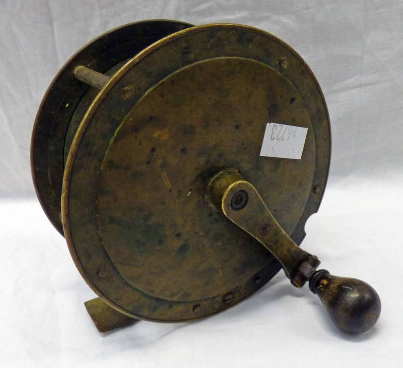 AN UNMARKED 'BRASS REEL WITH CUT-OUT FOR FOLDING HANDLE