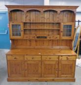 PINE DRESSER WITH 2 GLASS PANEL DOORS AND 2 DRAWERS OVER BASE OF 4 DRAWERS OVER 2 PANEL DOORS,