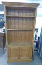 PINE BOOKCASE WITH SHELVES OVER 2 PANEL DOORS,