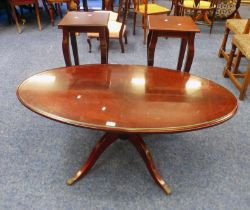 MAHOGANY OVAL COFFEE TABLE ON PEDESTAL WITH 4 METAL LION PAW FEET.