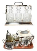 A Group of silver plate and pewter, including: an oblong tantalus with three cut-glass decanters and