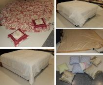 Assorted bedding and textiles comprising two cream bed spreads, red and white bed cover, matching