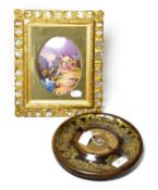 A Victorian circular brass inkstand dish, with pen and a Continental porcelain plaque depicting