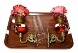 A pair of Victorian cranberry glass oil lamps . Both shades free from any cracks and majot chips.