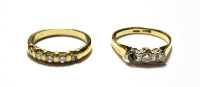 A diamond five stone ring, stamped '9K', finger size L1/2; and a diamond three stone ring,