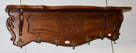 A carved oak hall rack with mask and scroll hooks, 110cm by 32cm by 25cm