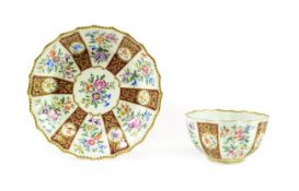 A Worcester Porcelain Tea Bowl and Saucer, circa 1770, of fluted form, painted with sprays of summer