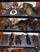 ~ A quantity of souvenir tribal masks from Africa and Malaysia (on 3 shelves)