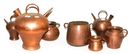 ~ A collection of antique copper vessels probably South American, including flagons and twin handled