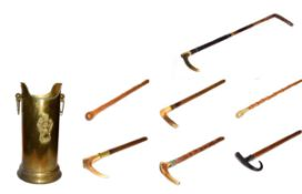 ~ A brass stick stand with loop handles containing six walking sticks and a riding crop, including