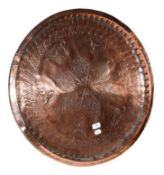 ~ A 19th century Continental copper serving tray with repoussé decoration, 85cm diamater