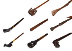 ~ A collection of carved walking sticks including African hardwood examples with figural and