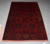 An Afghan Turkmen rug, the compartmentalised field enclosed by narrow borders, 195cm by 128cm